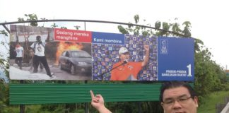 """""""Superman"""" Hew Kuan Yau showing his middle finger at a Barisan Nasional poster."""